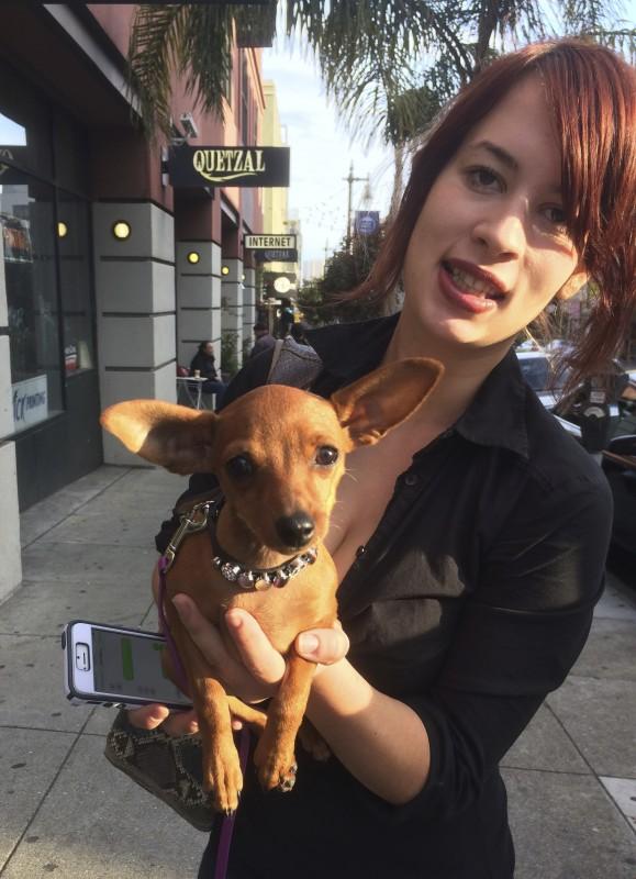 Woman Holding Miniature Pinscher Puppy In One Hand