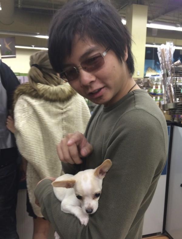 Man Holding White Chihuahua Puppy