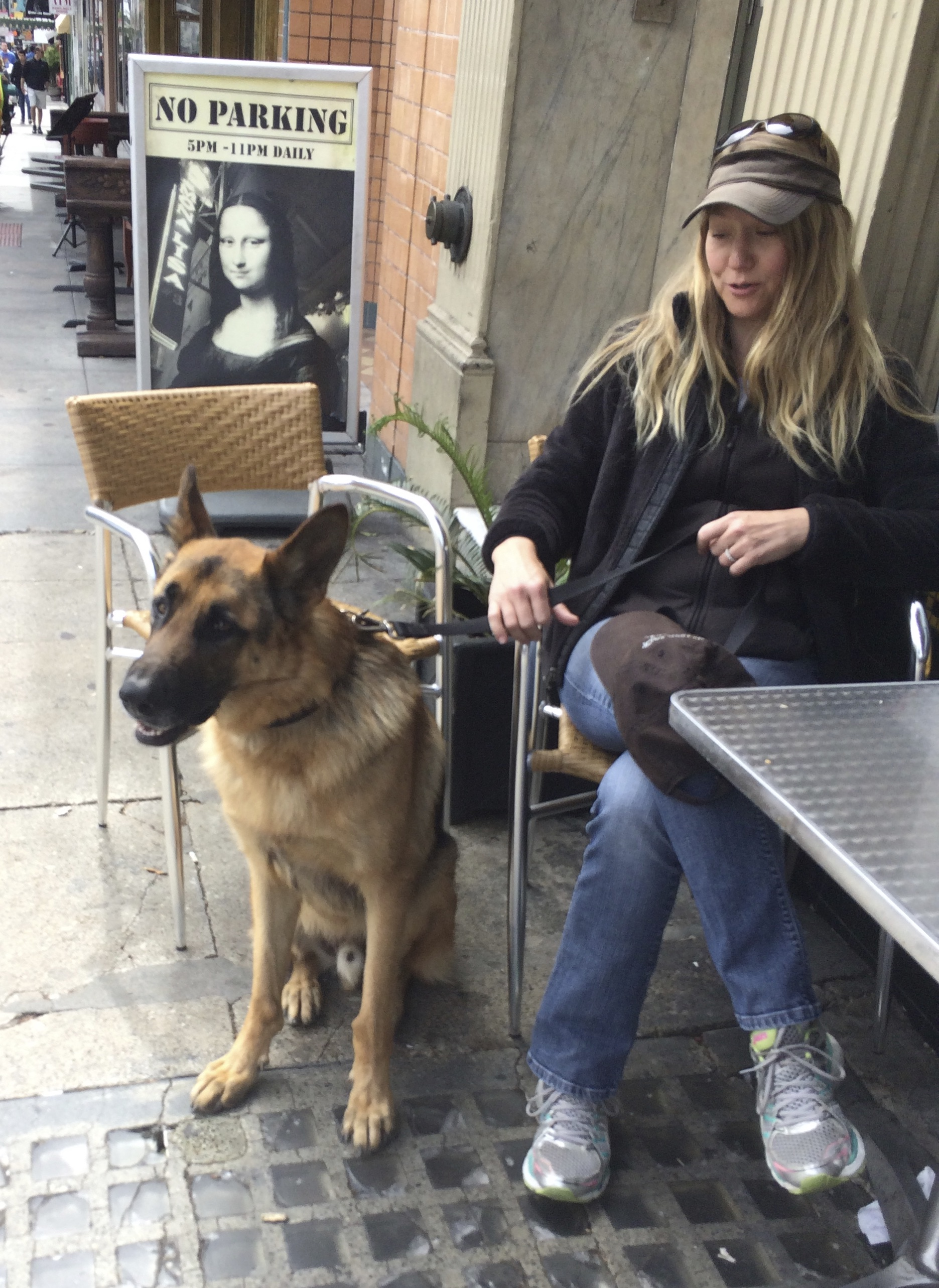 Woman Sitting With German Shepherd Who Is Pulling On His Leash
