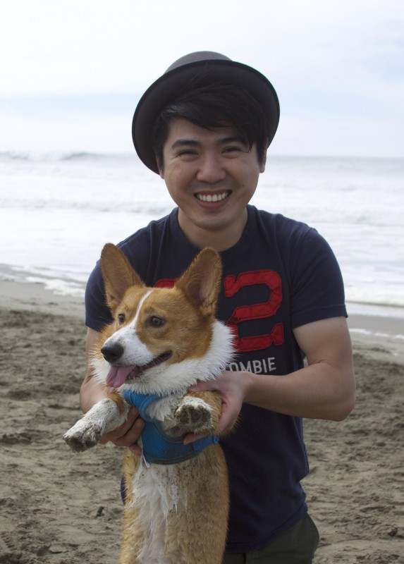 Man Holding Corgi Up On Beach