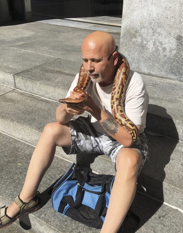 Man With Blood Python Sitting On Stairs
