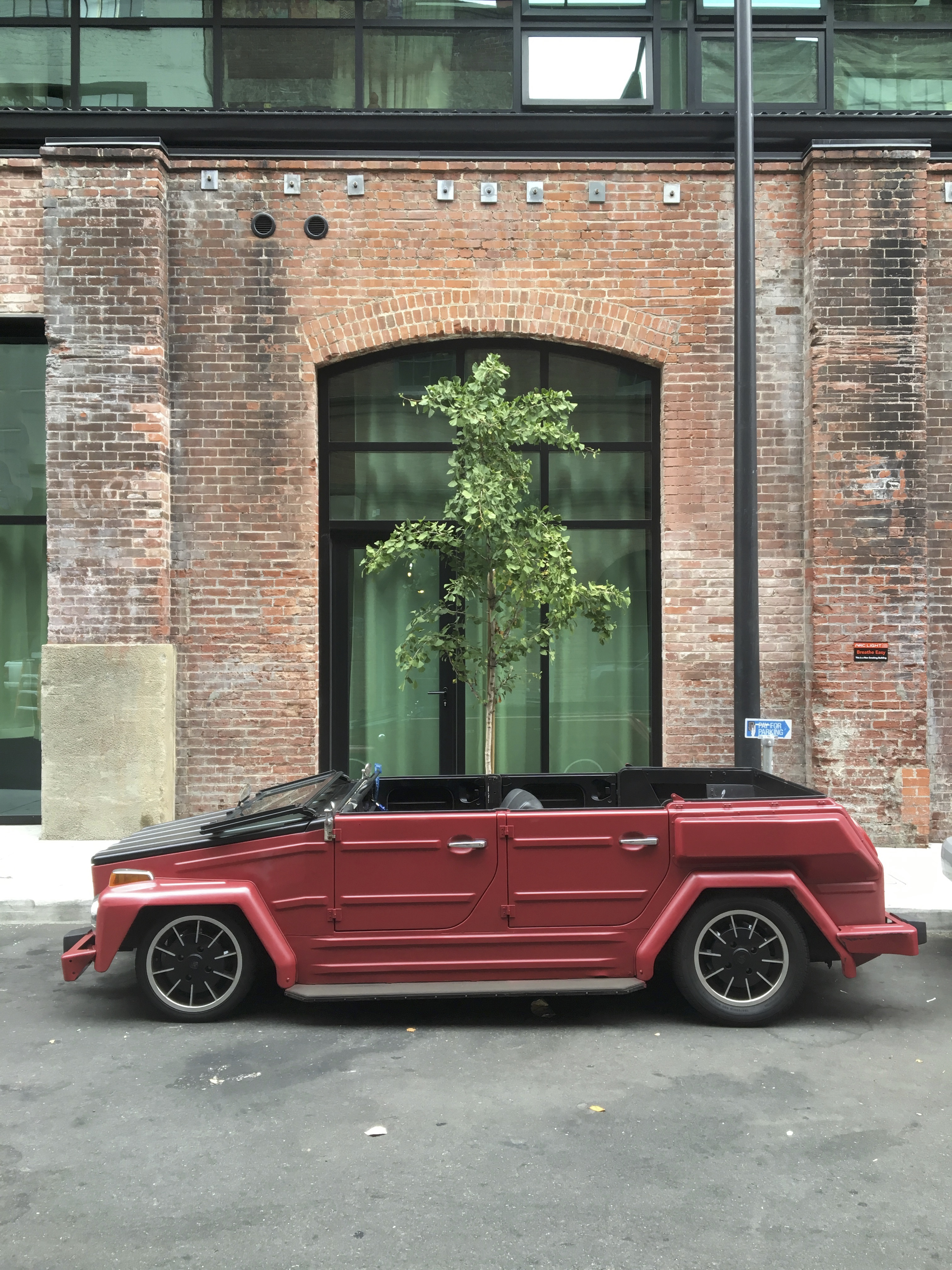 Volkswagen Thing Framed With Brick Building And Tree Behind