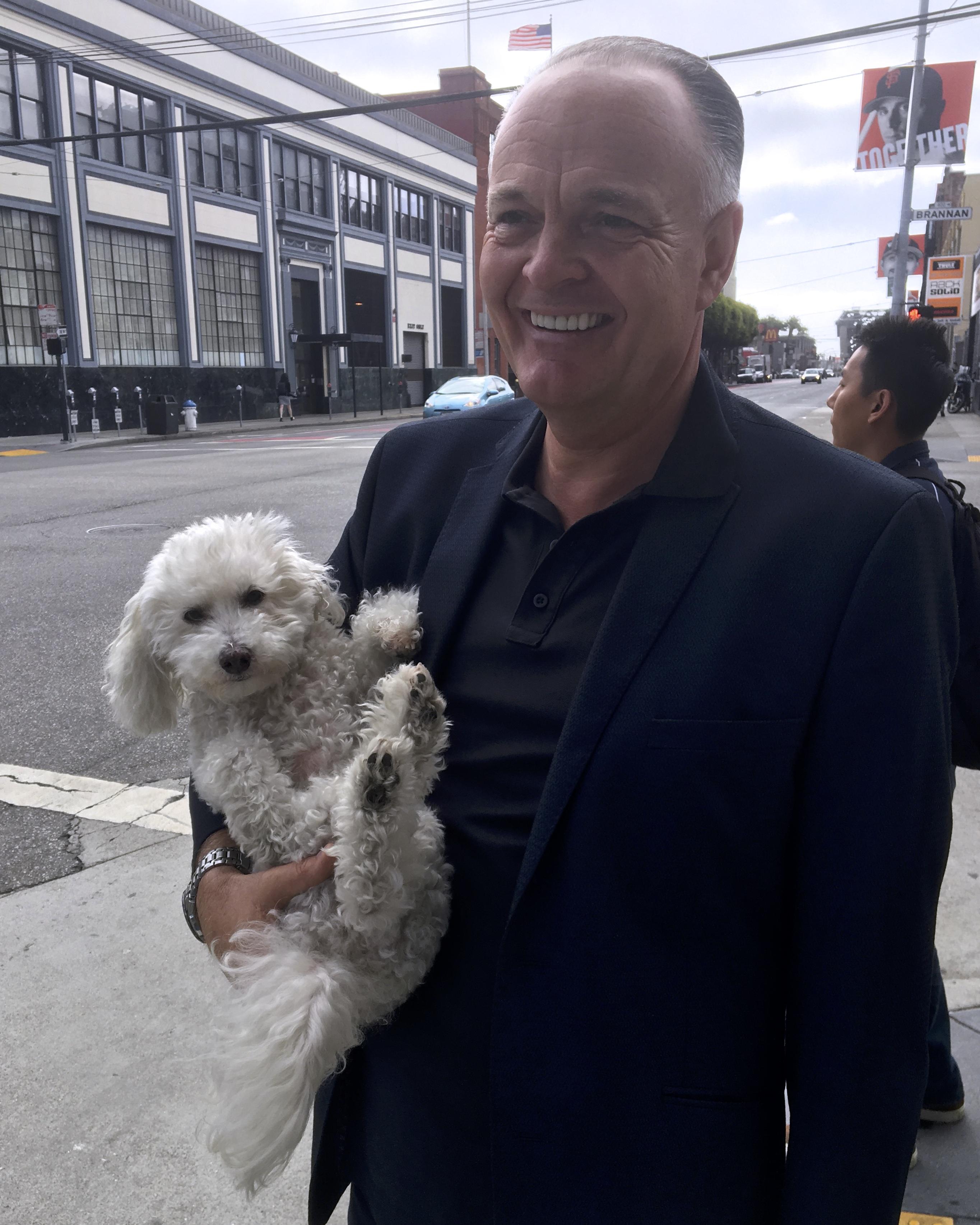 Man Holding Fluffy White Dog Upside Down Under One Arm