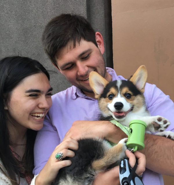 Man Holding Grinning Pembroke Corgi Puppy And Grinning While Woman Looks On And Grins Too