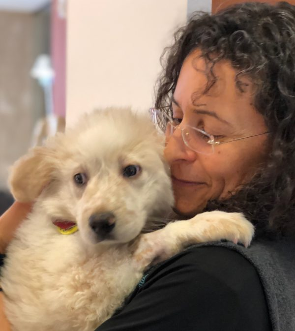 Woman Holding Beige Off-White Fluffy Mutt Puppy With Spots On Her Nose