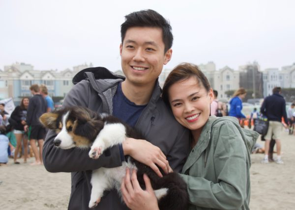 Grinning Couple Holding Tricolor Pembroke Welsh Corgi Puppy With One Flopped Ear