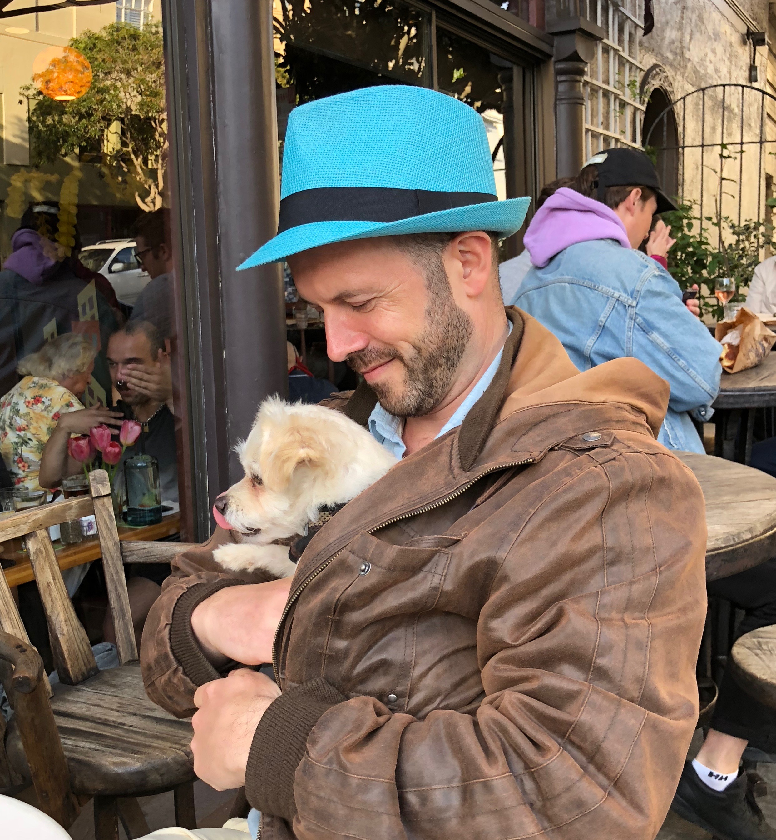 Man With Chihuahua Terrier Mix Cuddled In His Bomber Jacket