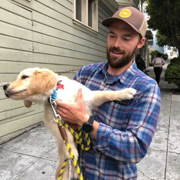 Man Holding Adorable Golden Retriever Puppy