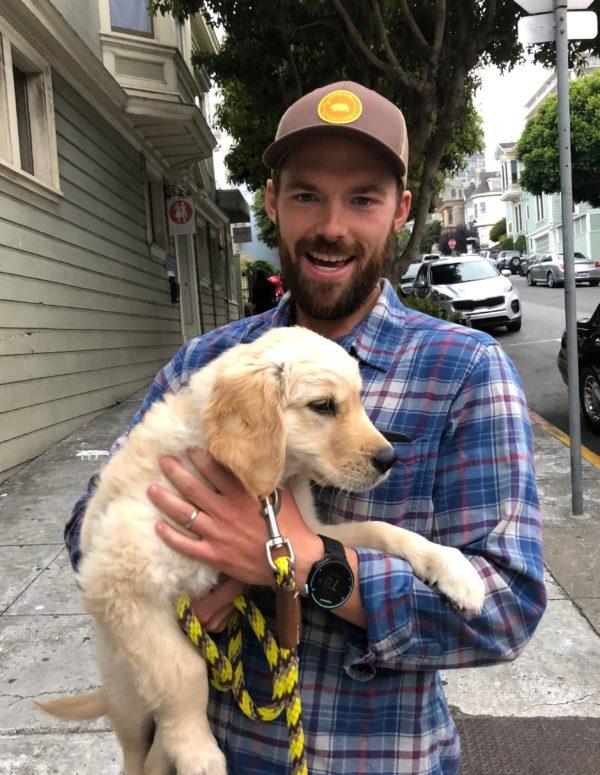 Man Holding Adorable Golden Retriever Puppy