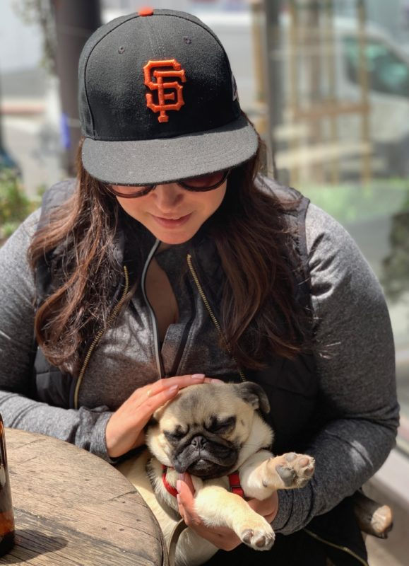 Woman Petting Pug Puppy