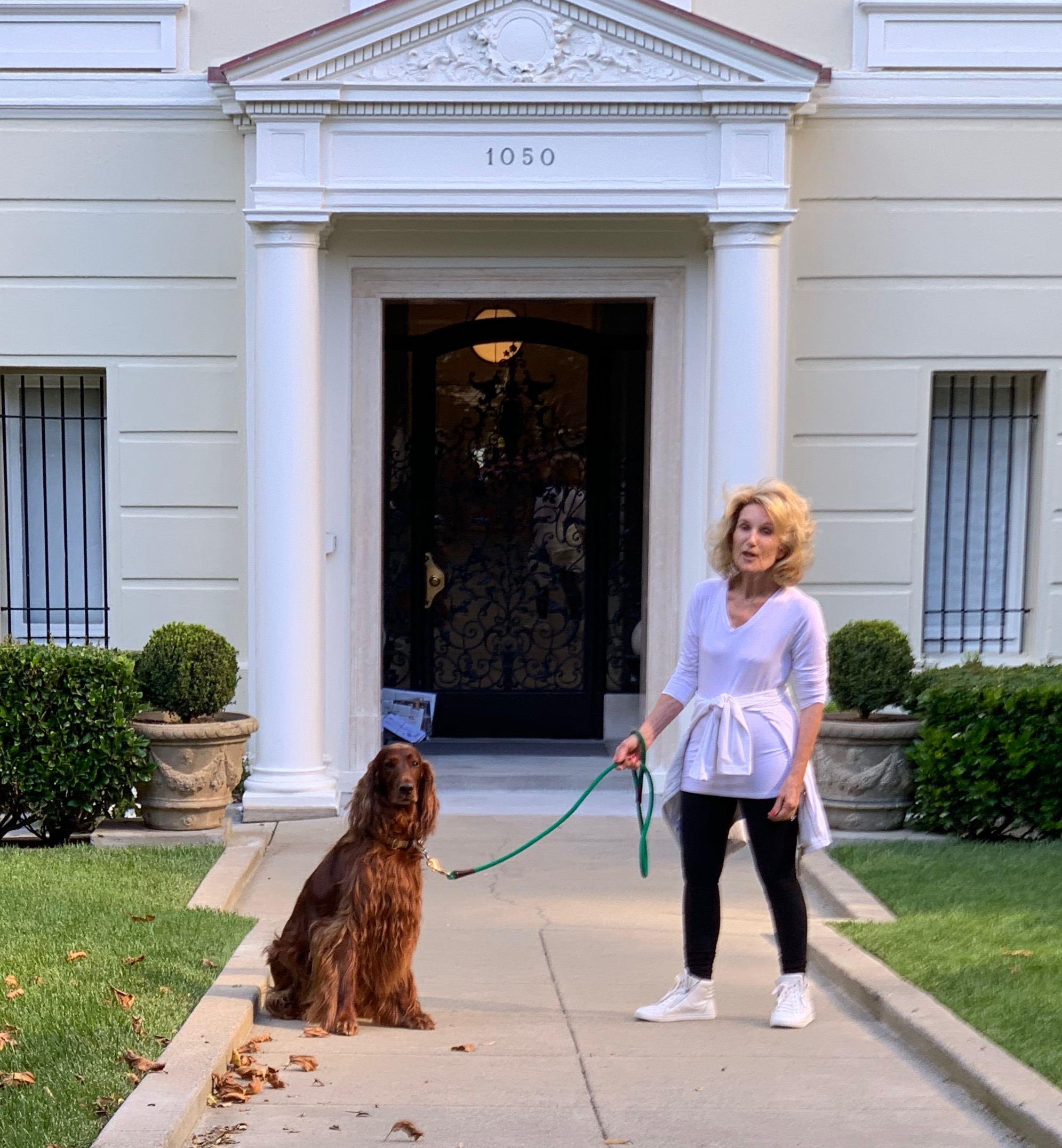 Woman And Irish Setter Standing In Front Of Their Front Door