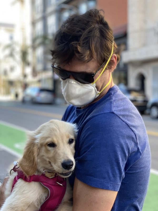 Man With Mask Holding Grinning Golden Retriever Puppy
