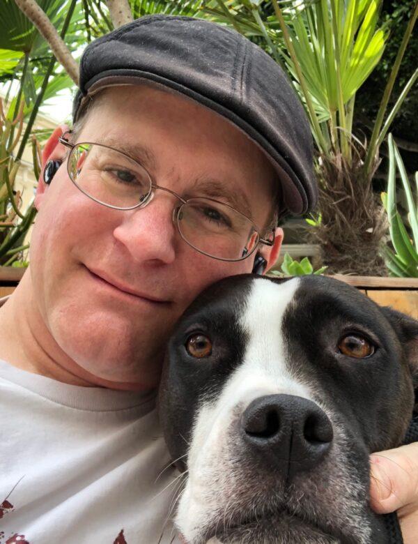 Man In Cap Hugging American Pit Bull Terrier