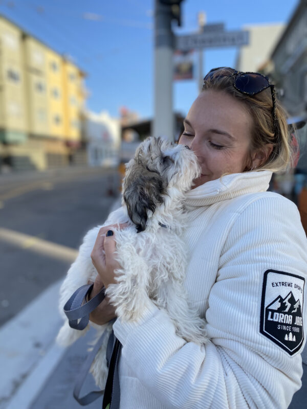 Woman Holding Havanese Puppy Who Is Licking Her Face